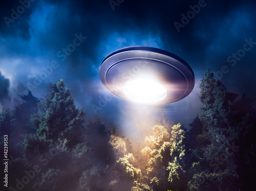 Canvas Print High contrast image of UFO flying over a forest with light beam at night