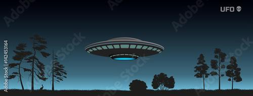 Fotografija Silhouette of UFO over a night forest