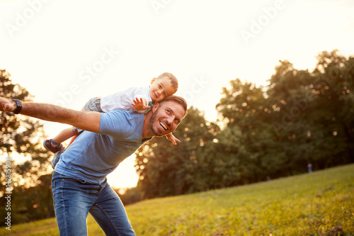 Father piggyback his son outside