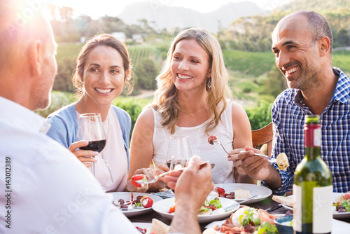 Mature friends enjoying eating