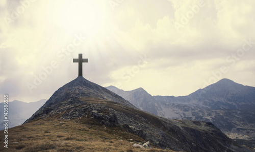 Photo Christian cross on top of the hill with sunrays, crucifixion, religious concept