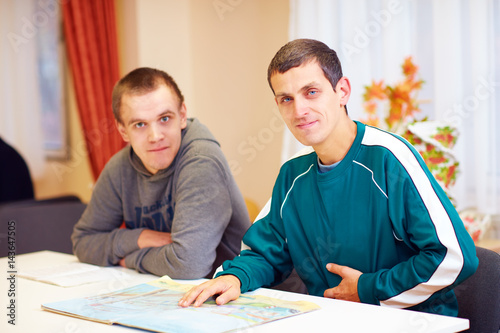 Canvas Print cheerful adult men with disability sitting at the desk in rehabilitation center