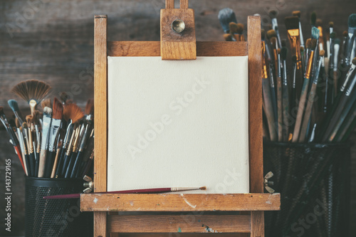 Photo Artistic equipment in a artist studio: empty artist canvas on wooden easel and paint brushes Retro toned photo