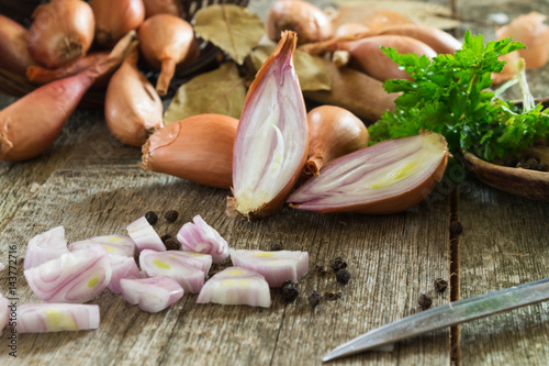 Whole and chopped shallot onion on a wooden background with green parsley leaves and a bay leaf. Shallow depth of field.