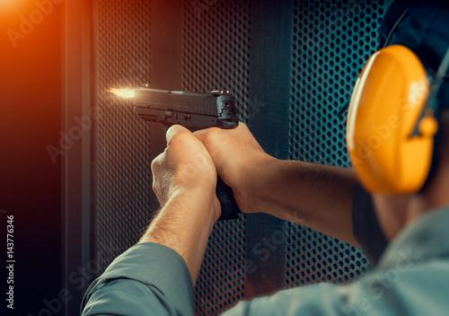 Fotografie, Tablou man firing pistol at target indoor shooting range