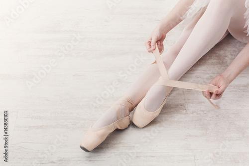 Ballerina puts on pointe ballet shoes, graceful legs