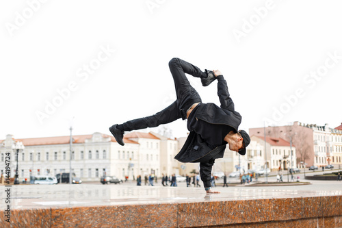 Canvas Print Stylish male dancer in black glasses and a cap dances on the street