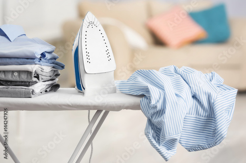 Fototapeta Electric iron and pile of clothes on ironing board