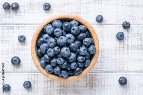 Foto Bowl of fresh blueberries on vintage white background. Top view