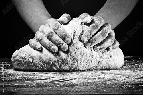 Woman's hands kneading the dough. In black and white style on dark background.