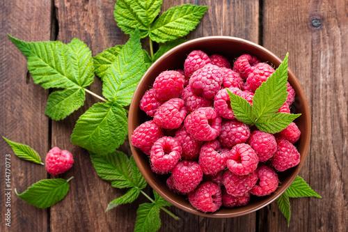 Carta da parati Fresh raspberry with leaves on wooden background