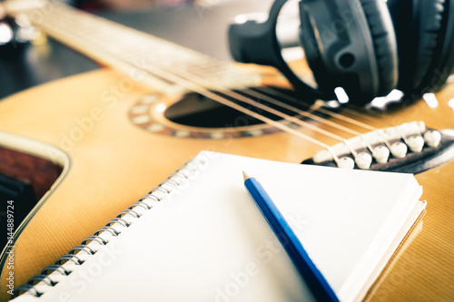 Obraz na plátně Guitar and Headphone with blank notebook for songwriting
