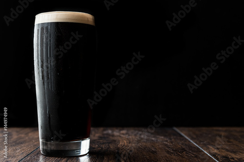 Photo Dark beer on wooden surface. copy space.