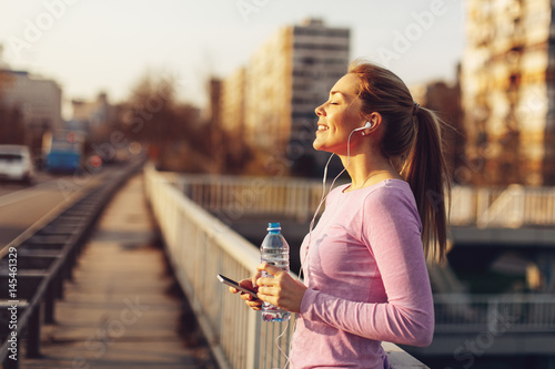 Photo Happy young woman listening to music after jogging at sunset