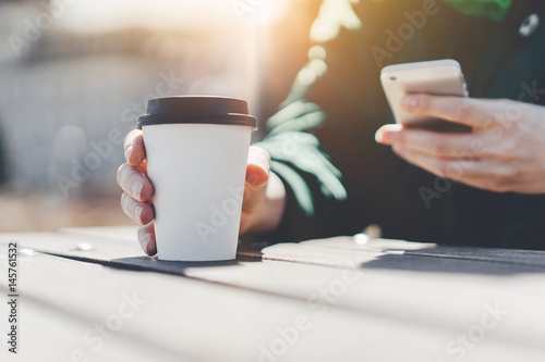 Fototapeta Hipster woman enjoying coffee to go and using her cellphone outdoor, Hipster wom