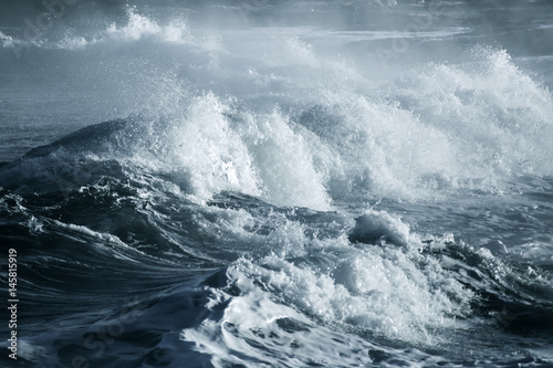 Leinwand Poster Big stormy ocean wave. Blue water background