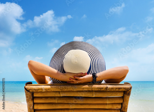 Fotomural Woman in hat relaxing on beach, looking at sea.
