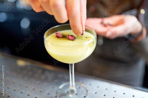 Fotografia, Obraz bartender decorating cocktail in glass at bar