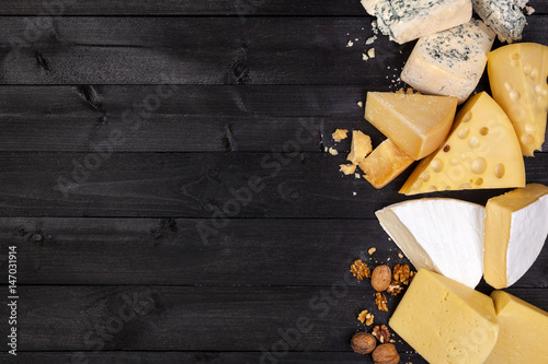 Various types of cheese on black wooden table. Top view. Copy space.