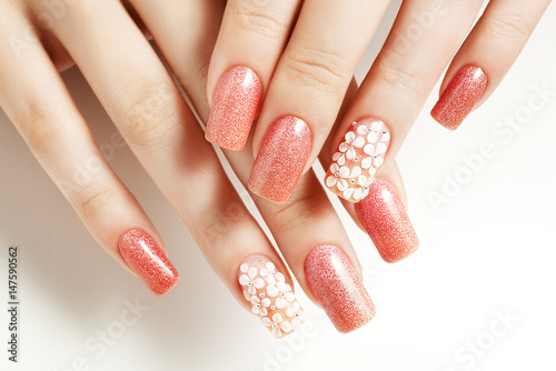 Photo Pink nails. Female manicure and floral patterns.