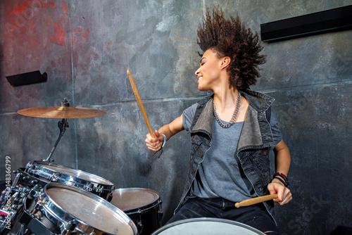 Vászonkép portrait of emotional woman playing drums in studio, drummer rock concept