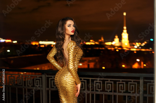 Valokuva Sexy fashionable beautiful young woman in long golden shining evening dress standing at balcony over view on night city lights in bokeh