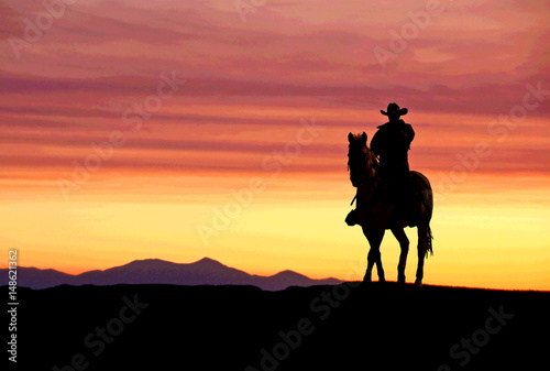 Fotografia Cowboy on horse at sunset in the American West