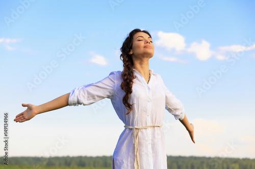 Slika na platnu Young happy woman in green field, evening light