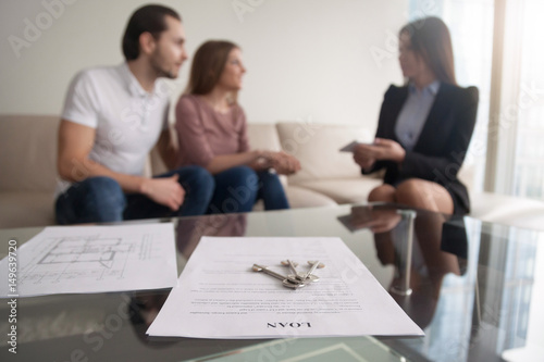 Obraz na płótnie Young family couple sitting on sofa discussing first mortgage with agent, focus