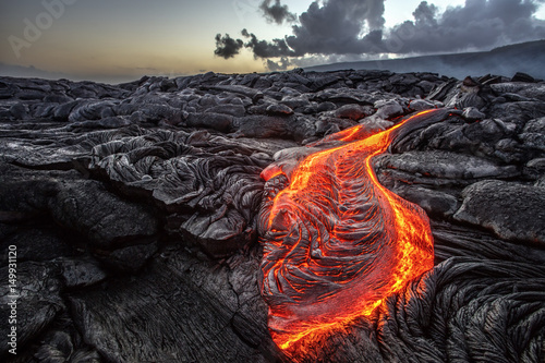 Canvas Print Red Orange vibrant Molten Lava flowing onto grey lavafield and glossy rocky land