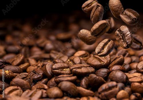 Fototapeta premium Spadające ziarna kawy. Ciemne tło z miejsca na kopię, zbliżenie
