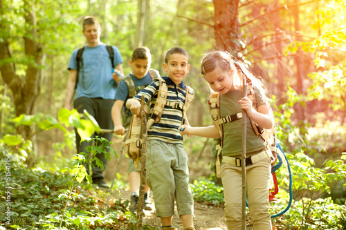 Children scouts and father explore the beautiful forest