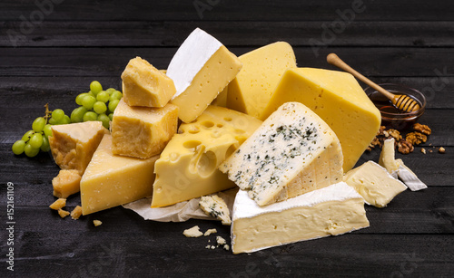 Canvas Print Various types of cheese on black wooden table.