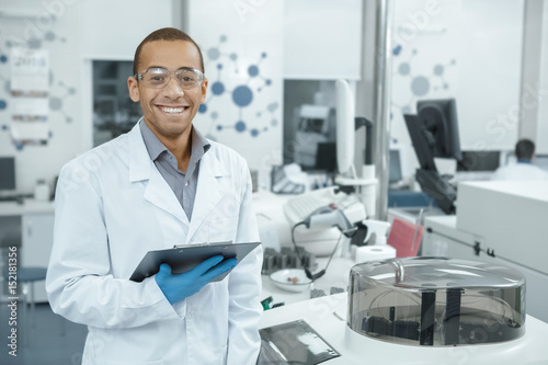 Fototapeta Young scientist watching laboratory machine during an experiment