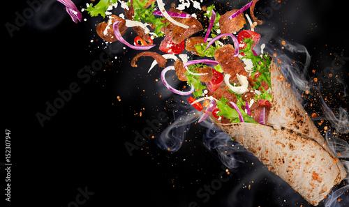 Kebab sandwich with flying ingredients.