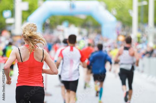 Woman running at marathon at start / finish