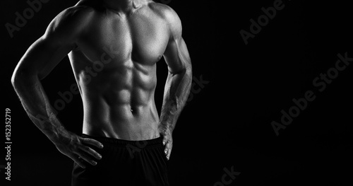 The torso of attractive male body builder on black background. Fotobehang