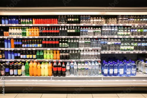 Different drinks in bottles on shelves of supermarket