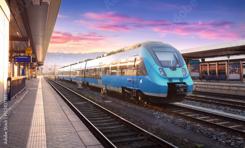 Beautiful view with modern high speed train on the railway station and colorful sky with clouds at sunset in Europe. Industrial landscape with blue train on railway platform. Railroad background