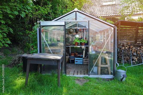 Valokuva petit serre en kit dans jardin particulier en été