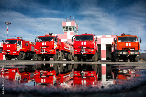 Valokuva Airfield fire trucks with reflection in a puddle near garage boxes