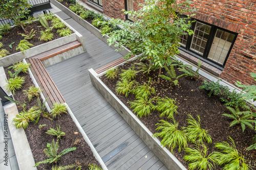 Fotografia Ogród na dziedzińcu z ławkami i drewnianym chodnikiem