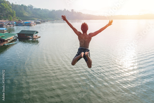 Fotografia Man jumping into lake retro on Longest wooden bridge in sangkhlaburi Thailand