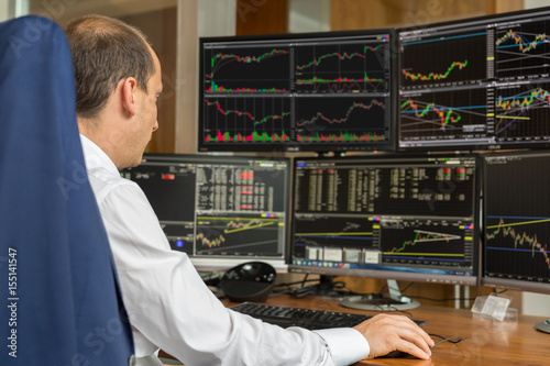 Rear view of stock trader looking and analyzing stock data at multiple computer screens Fototapet