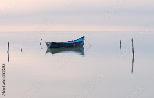 Old rowboat on the lake at sunset Fototapeta