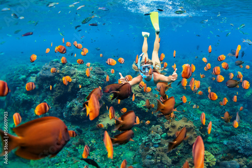 Photo Happy family - girl in snorkeling mask dive underwater with tropical fishes in coral reef sea pool