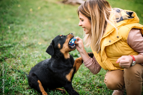 Fotografie, Obraz Girl playing with dog on grass - lifestyle details of woman playing with rottwei