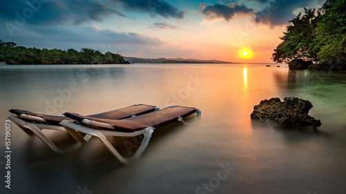 Foto Sunset with beach chairs on a tropical beach in Jamaica.