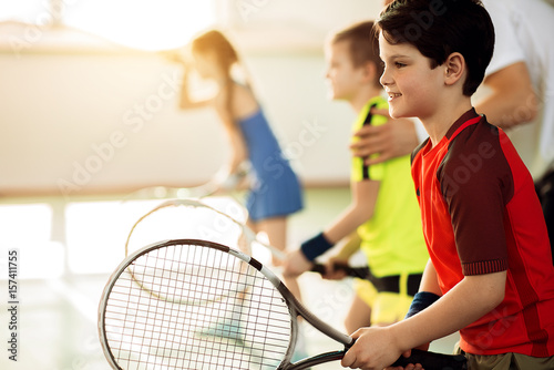 Excited children playing tennis on court