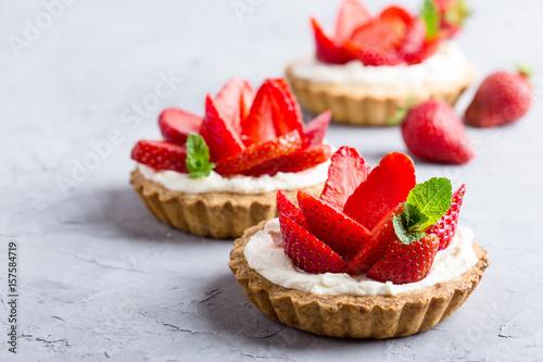 Obraz na płótnie Strawberry vanilla cream cheese tarts over light gray table